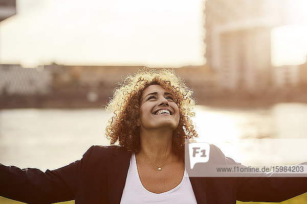 Smiling businesswoman looking at up with raised arms outdoors