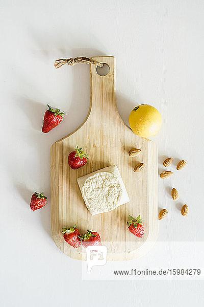 Wooden cutting board  fresh strawberries  almonds  single lemon and homemade vegan cheesecake