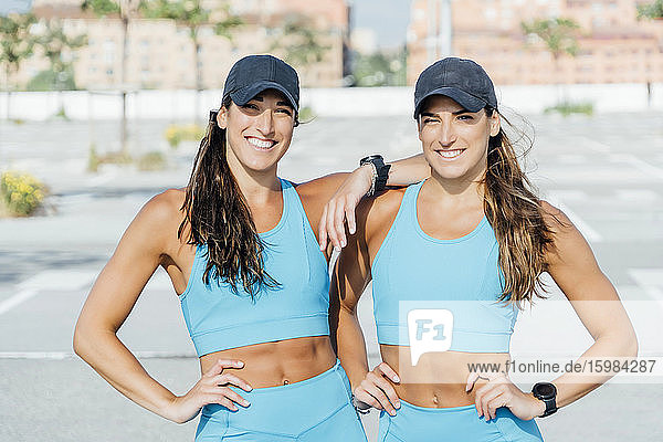 Portrait of smiling confident young twin sisters in sports clothing standing outdoors on sunny day
