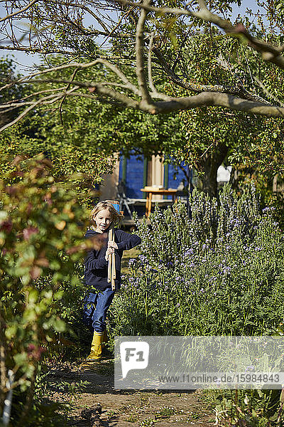 Girl in allotment garden carrying tools