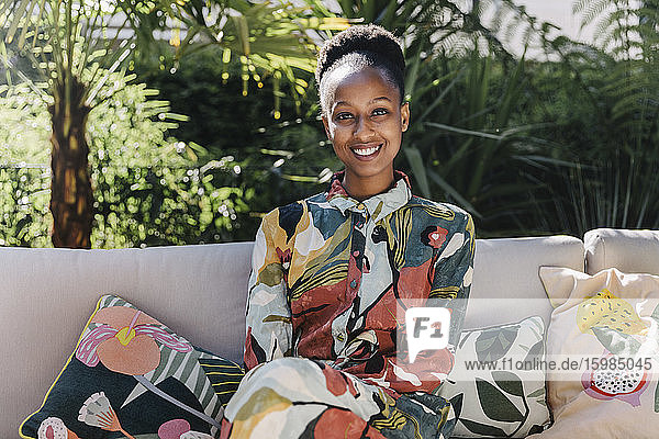 Portrait of happy young woman wearing fashionable dress relaxing on couch in garden