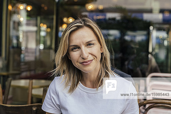 Portrait of smiling woman in front of a coffee shop