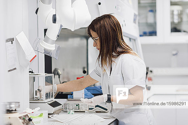 Confident female technician holding pills while working at laboratory