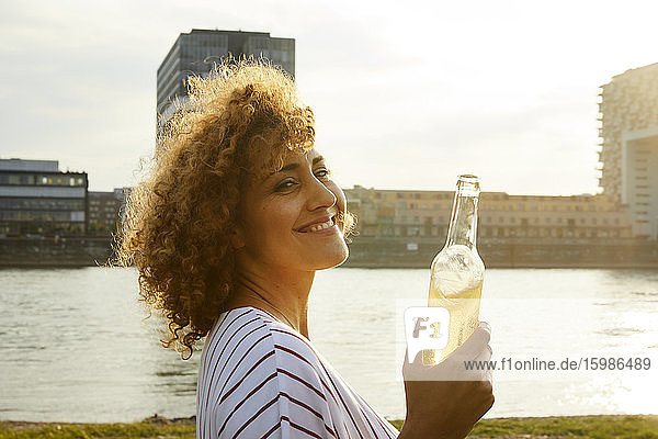 Portrait of smiling woman with glass bottle at riverside
