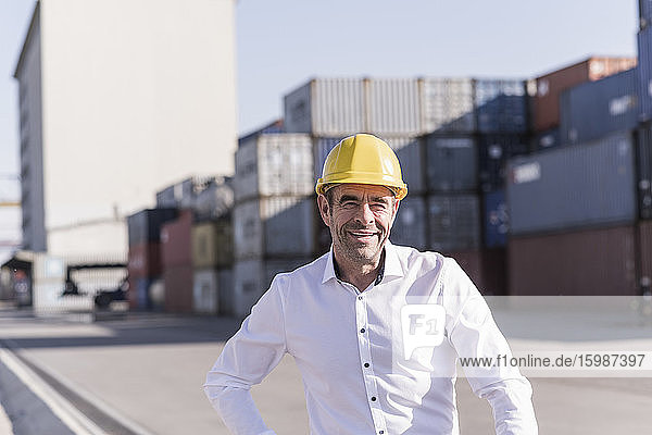 Portrait of smiling businessman wearing safety helmet in front of cargo containers