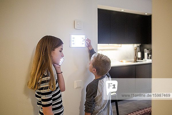 Girl talking on smart phone while brother using digital tablet on wall at home