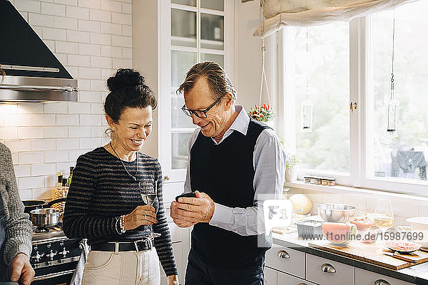 Smiling man and woman sharing smart phone while standing in kitchen