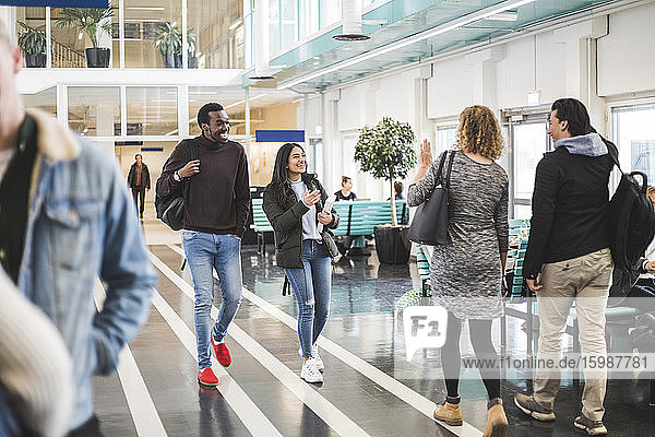 Young male and female students walking in cafeteria at university