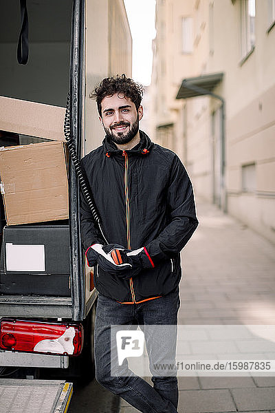 Portrait of confident young delivery man with boxes in truck