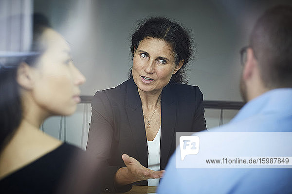 Confident mature female financial advisor discussing with businessman and businesswoman during meeting at office