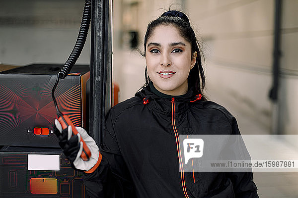 Portrait of confident young delivery woman by truck