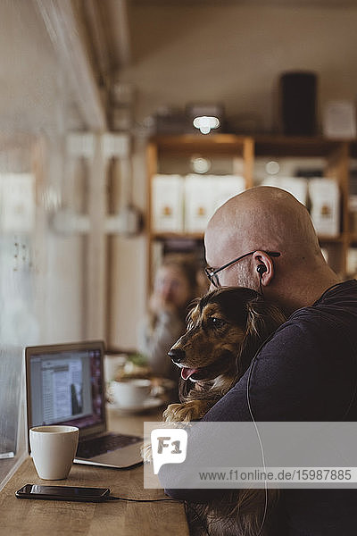 Bald man sitting with dog while using laptop at cafe