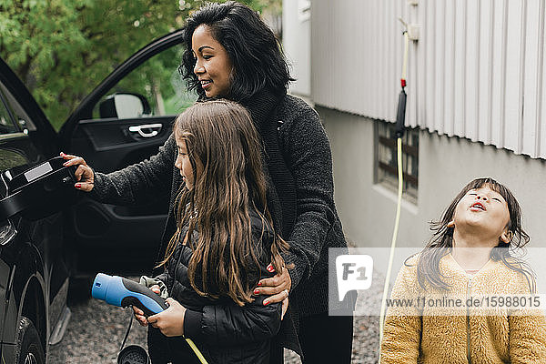 Woman teaching daughter to charge electric car at charging station