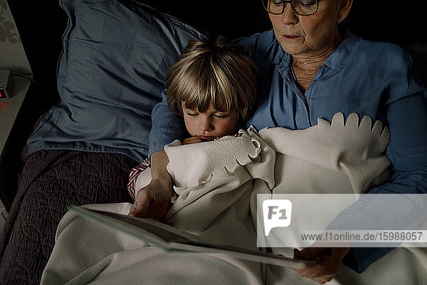 High angle view of grandmother reading story book for grandson on bed at home