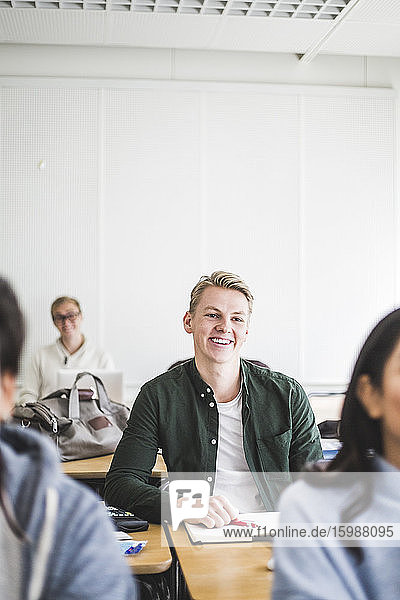 Smiling young man sitting at desk in classroom