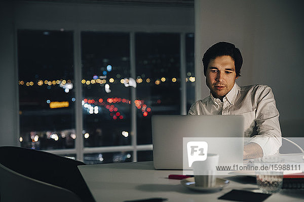 Confident businessman using laptop while sitting at desk in creative workplace