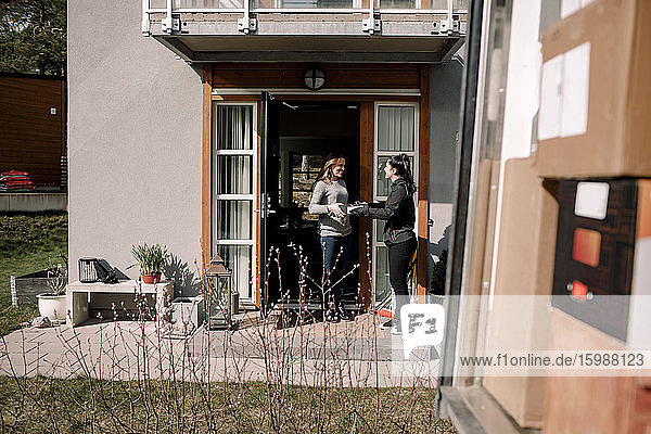 Delivery woman delivering package to customer at entrance of house