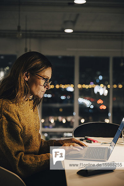 Side view of female professional working late while using laptop at illuminated desk in office
