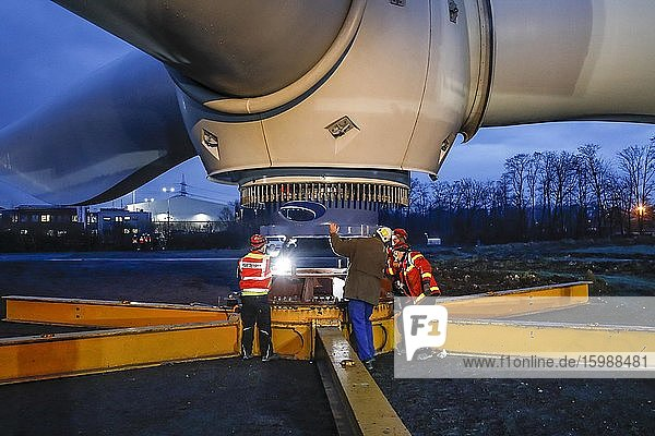 Montage einer Windkraftanlage  Krane heben in der Dämmerung Rotorkranz mit Rotorblättern  Bottrop  Ruhrgebiet  Nordrhein-Westfalen  Deutschland  Europa