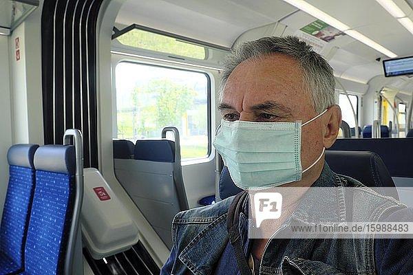 Mann mit Mundschutzmaske in der S-Bahn  Coronakrise  München  Bayern  Deutschland  Europa