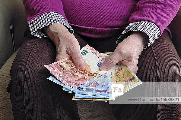 Hand of a senior citizen with euro notes  counting her money  Munich  Bavaria  Germany  Europe