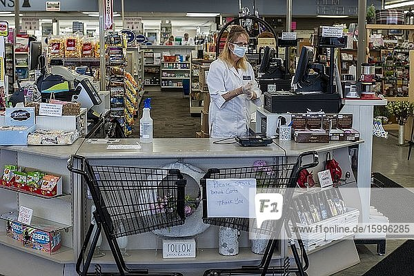 St. Paul  Minnesota  A cashier in a drugstore puts on her protective gloves while shopping carts keep people at a distance when paying for their purchases at the counter.