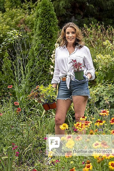 A pretty 37 year old redheaded woman in a garden setting surrounded by annual and perennial plants in the early summer.