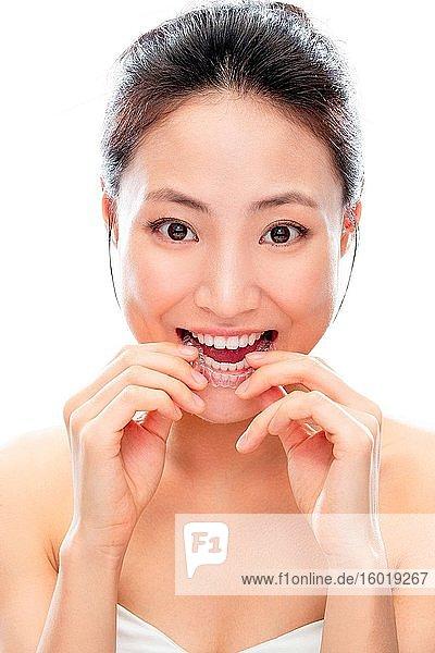 Junge Frau trägt eine durchsichtige Zahnspange
