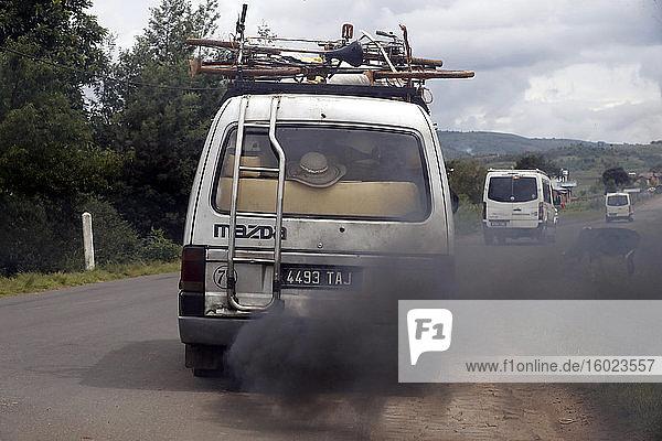 Alter Kleinbus mit schwarzem Rauch auf der Straße