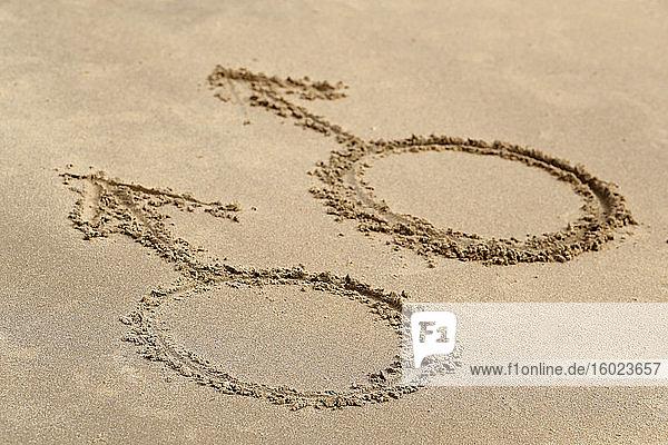 Männliche Geschlechtssymbole auf Sandstrand geschrieben