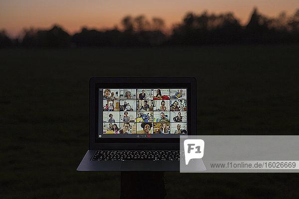 Video-Chat mit Freunden am Laptop-Bildschirm im Garten in der Abenddämmerung