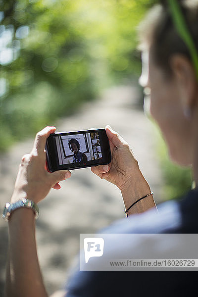 Woman video chatting with friends on smart phone screen