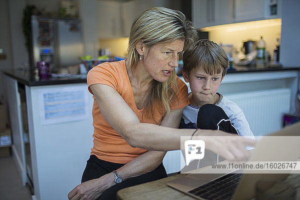 Mother helping son with homework at laptop