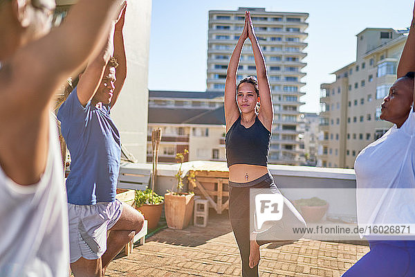 Young friends practicing yoga tree pose on sunny urban rooftop balcony