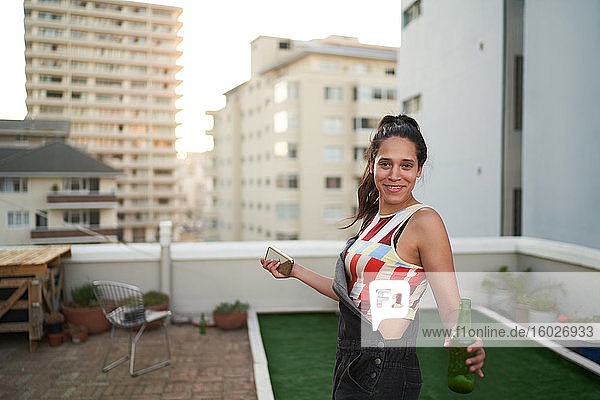 Portrait confident young woman with smart phone and beer on rooftop