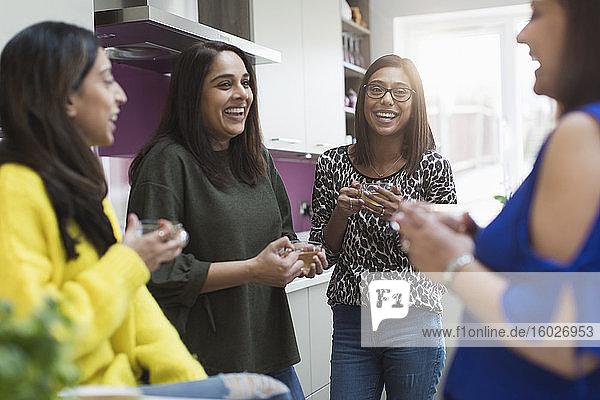 Happy Indian women drinking tea in kitchen