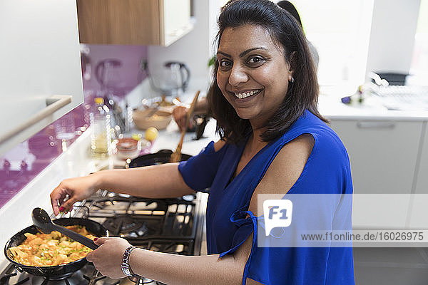 Portrait happy Indian woman cooking food at stove in kitchen