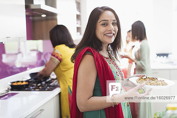 Portrait happy Indian woman in sari cooking food in kitchen