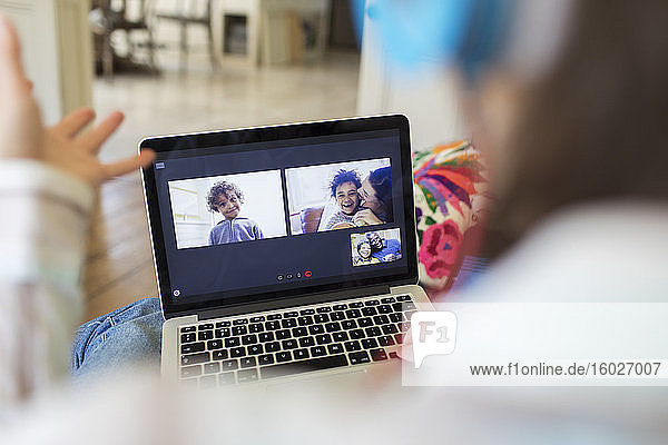 Woman video chatting with family on laptop screen