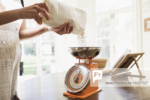 Woman measuring flour for baking in kitchen