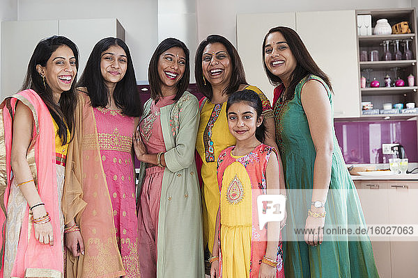 Portrait happy Indian women and girls in saris in kitchen