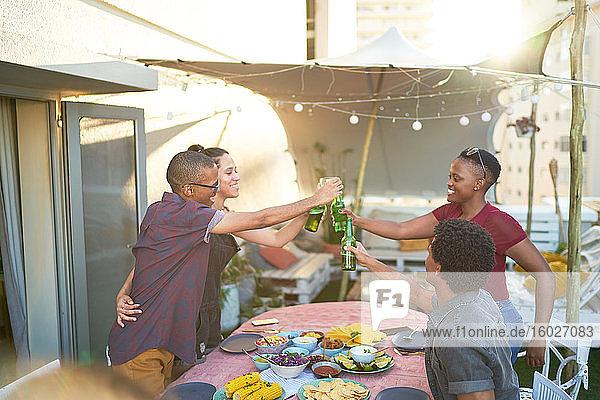 Fröhliche junge Freunde stoßen auf Bier über dem Terrassentisch an