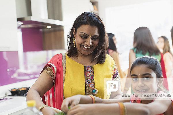 Indische Mutter und Tochter in Saris kochen Essen in der Küche