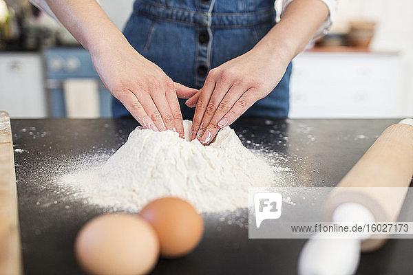 Nahaufnahme eines Teenager-Mädchens  das ein Mehlnest auf der Küchentheke baut