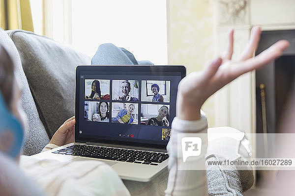 Junge Freunde im Videochat am Laptop-Bildschirm auf dem Sofa