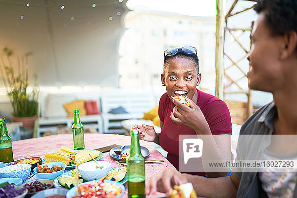 Portrait happy young woman eating taco at patio table