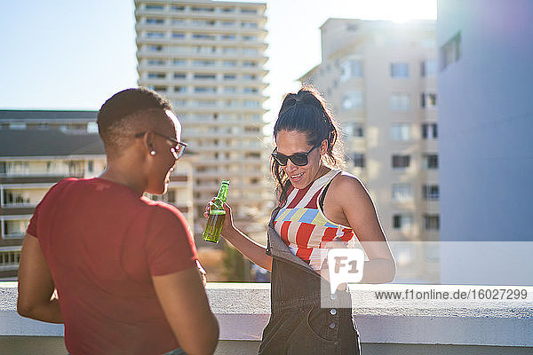 Carefree young woman dancing and drinking beer on sunny urban rooftop