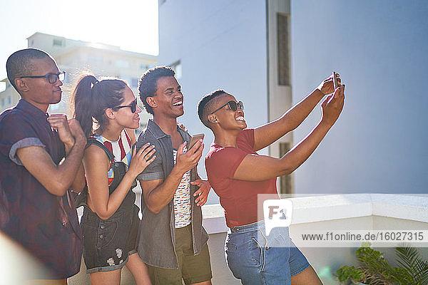 Fröhliche junge Freunde auf dem sonnigen Stadtbalkon