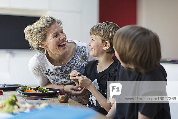 Happy mother and sons eating dinner at table