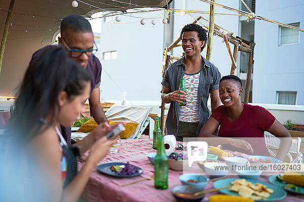 Happy young friends enjoying dinner on rooftop balcony